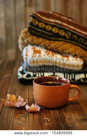 Stack of cozy knitted sweaters and cup of hot tea on wooden table