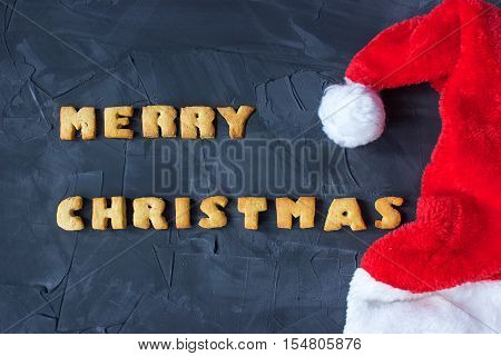 christmas background with Santa's cap and baked gingerbread words merry christmas on the concrete background. creative idea
