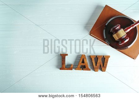 Word law with judges gavel and legal book on wooden background
