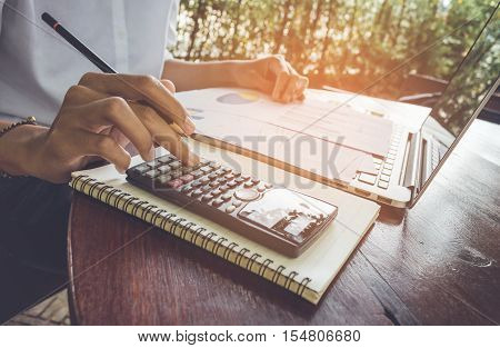 business woman calculate and analyzing graph document financial with laptop vintage tone.
