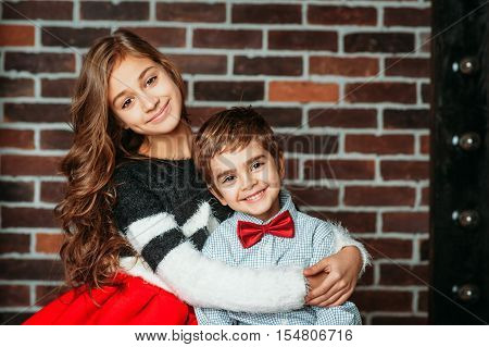 Little boy and girl smiling and hugging on brick background in fashion clothing. Kids brother and sister are happy and love each other. Concept togetherness, family, friendship, relations, emotions.