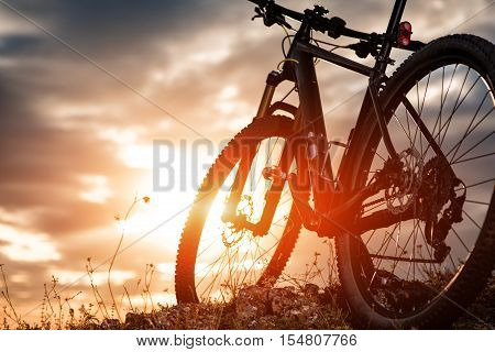 Mountain bike standing against cloudy sky against sunset