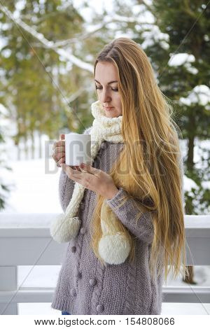 Young beautiful woman with blond hair outdoor with cup of hot coffee wearing knitted warm sweater. Winter confort concept.