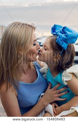 little girl three years sitting on the lap of the mother with long blond hair and they are dressed in blue dress and large blue bow on her head , sitting at the pier by the sea with yachts at sunset