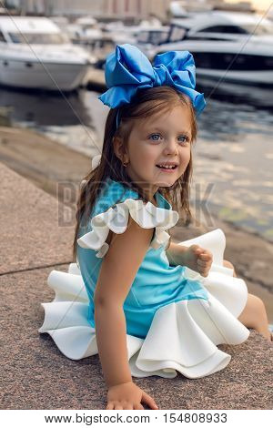 portrait of a little girl three years with the blue bow on her head, which is smiling and looking forward interested