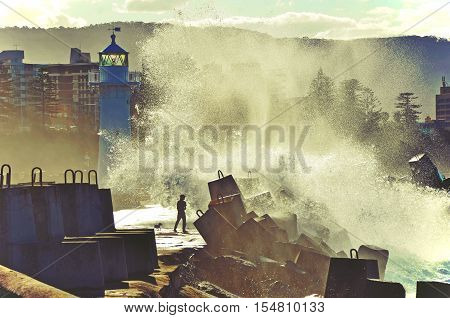 Big waves breaking over man and dog on Wollongong harbor break wall and lighthouse, Wollongong, New South Wales, Australia. Toned image