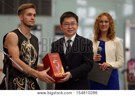 ST. PETERSBURG, RUSSIA - OCTOBER 20, 2016: Representative of China Southern Airlines give the prize to the member of St. Petersburg Wushu team during the China Day in airport Pulkovo
