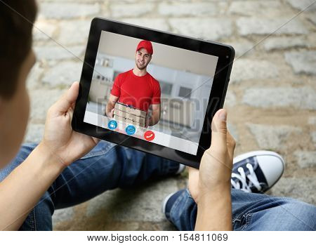 Man using tablet for online pizza order. Video call and chat concept. Modern communication technology.