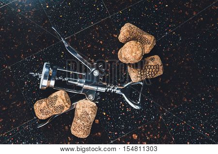 corkscrew with corks lies on a stony table-top