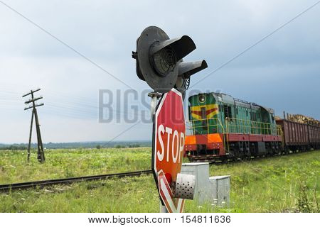 Traffic lights and signs at the railroad crossing and the approaching freight train (Ukraine).