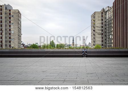 Katowice Poland - May 2 2016: Young man sending sms in the city center among high blocks of apartments