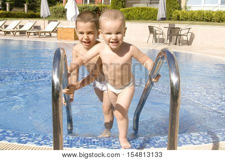 Two little boys, five and four years near swimming pool.