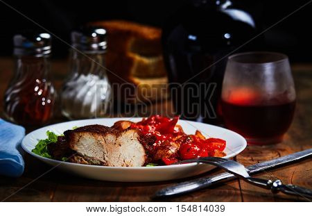 Roast lamb with fruit and vegetable garnish and wine. Cutlery on a wooden table and blue cloth with glass salt shakers and pepper shakers.