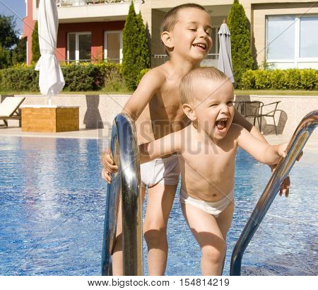 Two litle boys of ffour and five years near swimming pool