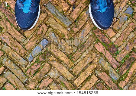 Old Cobble Stones In A Herringbone Pattern With Toes Of Modern Training Shoes