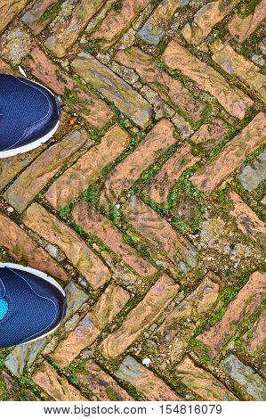 Toes Of Modern Training Shoes Standing On Old Cobble Stones In A Herringbone Pattern