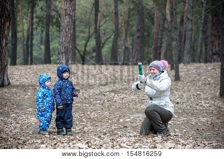 Two little brothers playing together with their mother at autumn forest. Mom is going to use petard.