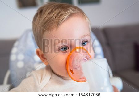 Little boy taking inhalation therapy by the mask of a nebuliser