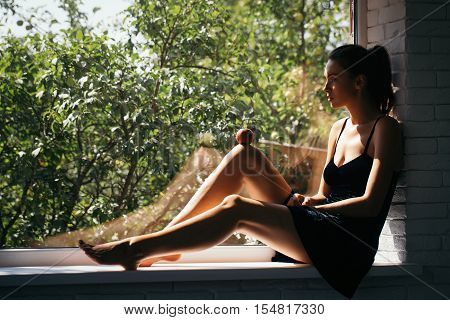 Young girl with pretty cute face in black sexy dress with long legs sitting relaxing on window sill with red apple on her knee on background of green trees indoor