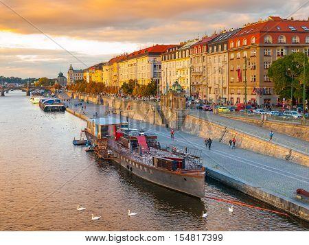 Evening view of Rasin Embankment with boats on Vltava River in Prague, Czech Republic