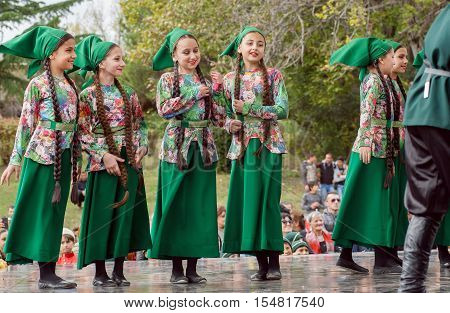 MTSKHETA, GEORGIA - OCT 14, 2014: Unidentified girls in traditional Georgian costumes playing on stage of party on the City Day on October 14, 2016. Mtskheta has a population 20.000