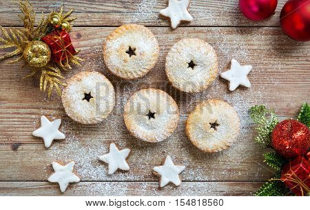 Mince pies and cinnamon stars with christmas decorations on wooden table