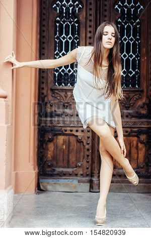 pretty girl in white dress high heels with long hair leaning on wall and touching ankle on ancient wooden door background