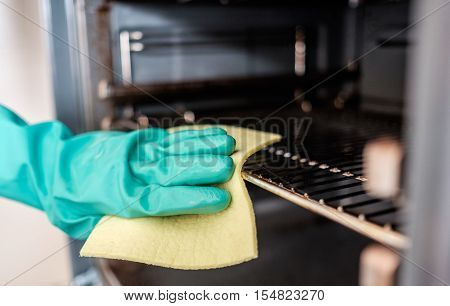 Man's hand cleaning the kitchen oven door