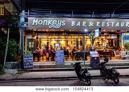 Koh Chang, Thailand - December 20, 2015: People dine at outdoor restaurant bar located on the main road of White Sands Beach. There are many restaurants that provide International or Thai dishes