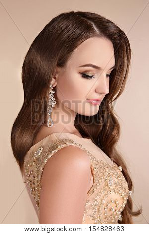 Makeup. Elegant Lady Portrait, Sensual Brunette Woman With Shiny Wavy Silky Hair And Fashion Earring