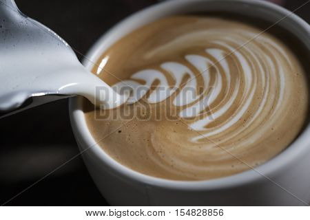 Making latte Art on a Cappucinno. Freshly made