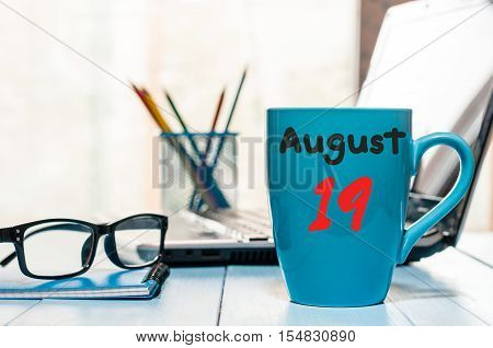 August 19th. Day 19 of month, morning coffee cup with calendar on audit office background. Summer time. Empty space for text.