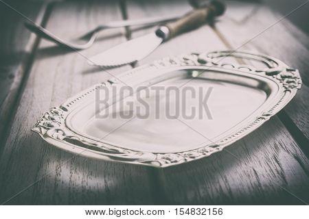 Vintage pewter plate fork and knife on old dark wooden board