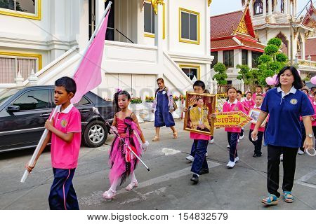 Bangkok, Thailand - January 8, 2016: Pupils of the school holds the portrait of Thai King Bhumibol Adulyadej during procession through the streets of the city. The king is highly revered in Thailand.