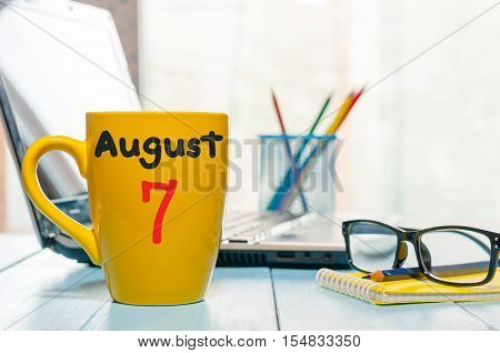 August 7th. Day 7 of month, morning yellow coffee cup with calendar on business background. Summer time. Empty space for text.