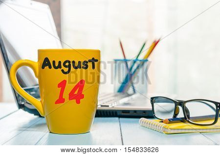 August 14th. Day 14 of month, morning yellow coffee cup with calendar on IT-office background. Summer time. Empty space for text.