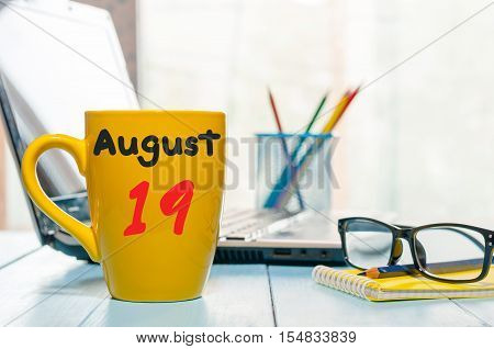August 19th. Day 19 of month, morning yellow coffee cup with calendar on audit office background. Summer time. Empty space for text.