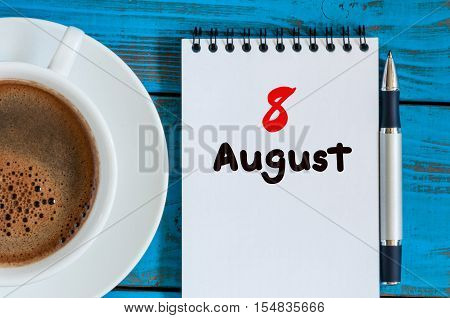 August 8th. Day 8 of month, loose-leaf calendar on blue background with morning coffee cup. Summer time. Unique top view.