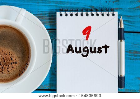 August 9th. Day 9 of month, loose-leaf calendar on blue background with morning coffee cup. Summer time. Unique top view.