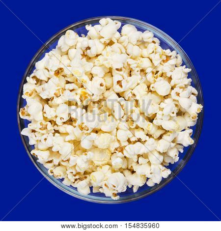 Popcorn in glass bowl on blue background. Butterfly shaped popped popcorn puffed up from the corn kernels, after it has been heated. Edible and vegan food. Isolated macro photo close up from above.