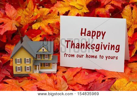 Happy Thanksgiving greeting Some fall leaves and yellow and gray house and greeting card with text Happy Thanksgiving from our home to yours