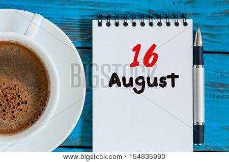 August 16th. Day 16 of month, loose-leaf calendar on blue background with morning coffee cup. Summer time. Top view.