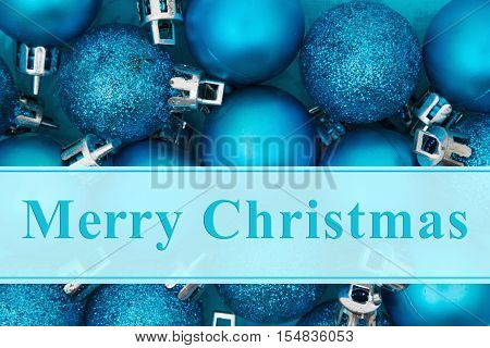 Merry Christmas greeting Some bright blue sparkle and matte Christmas ball ornaments with text Merry Christmas