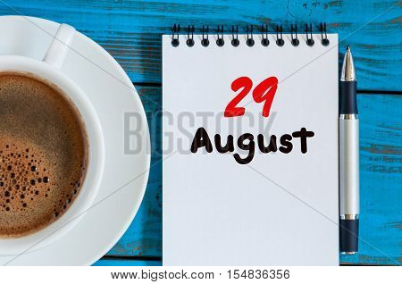 August 29th. Day 29 of month, loose-leaf calendar on blue background with morning coffee cup. Summer time. Top view.