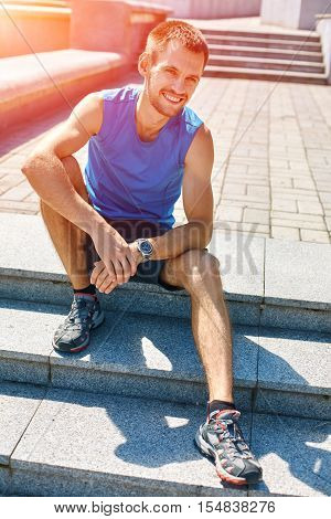 man sitting and resting on the steps. man runner athlete warming up before jogging along a city bay at the early morning. man fitness sunset jogging workout wellness concept.
