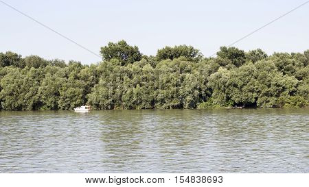 Danube River with Fishing Boat in the distance And Treeline in the Background