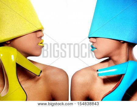 High fashion look.glamour fashion beautiful black American woman with blue and yellow bright lips with blue and yellow material with blue and yellow open-toe in hand