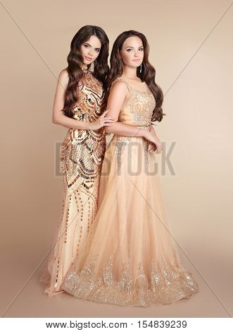 Two Fashion Ladies. Beautiful Women With Wavy Hair Wears In Long Golden Dress Isolated On Beige Stud