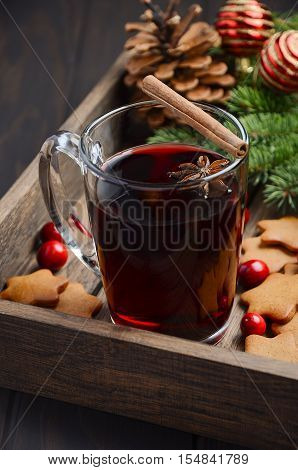 Christmas mulled wine. Holiday concept decorated with Fir branches, Gingerbread Cookies and Cranberries on dark wooden tray. Selective focus.