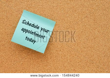 A reminder to make an appointment Bulletin board with a blue sticky note with text Schedule your appointment today